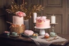 De lijst van het luxehuwelijk met een mooie roze cake verfraaide met mastiek en nam goud in antiek klassiek binnenland toe Stock Foto