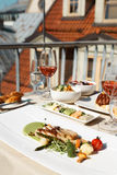 De lijst voor twee met voedsel bij dakrestaurant, geroosterde vissen versiert Stock Foto