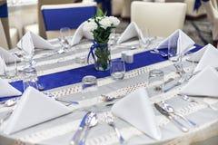 De lijstopstelling van het ontvangstdiner met vaatwerk, servet, lepel, vork en glazendecoratie met de blauwe streep van de sjerpd royalty-vrije stock foto's