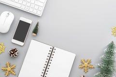De de lijstvlakte van het Kerstmisbureau legt met computer draadloos toetsenbord, muis, smartphone, leeg notitieboekje, minikerst stock afbeelding