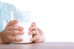 De lilla händerna av ungen rymmer lite ett stort exponeringsglas av mjölkar, som står på en trätabell som isoleras på en vit bakg Royaltyfri Bild