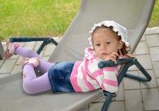 De lilla ledsna flickalögnerna i en chaise är slö arkivbilder
