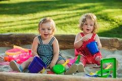 De lilla tvåna behandla som ett barn flickor som spelar leksaker i sand Royaltyfri Fotografi