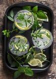 De limonade van tuinkruiden Gegoten water met citroen, rozemarijn, thyme, salie en munt op houten achtergrond, hoogste mening royalty-vrije stock fotografie