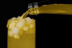 De limonade wordt gegoten in het glas, op een zwarte achtergrond Stock Afbeeldingen