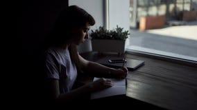 De linkerhand van een jonge vrouw trekt met een potlood op document dichte omhooggaand stock videobeelden