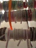 De lintband rolt in diverse kleuren en vormen, hangend in vertoning bij een kleine winkel stock foto