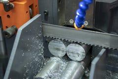 De lintzaagmachine die ruwe metalenstaven snijden stock foto's