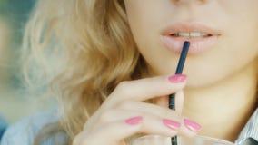 De lippen van een jonge sensuele vrouw die een cocktail van de buis, het glimlachen drinken stock video