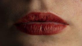 De lippen van het meisje worden slecht gemaakt omhoog door lippenstift stock foto