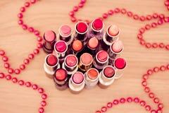 De lippenstiften van de aantrekkingskracht en rode geparelde halsband royalty-vrije stock foto