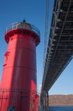 De littl rode vuurtoren en de grote grijze brug Royalty-vrije Stock Afbeeldingen