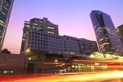 De ljusa slingorna av bilarna i den moderna staden Royaltyfri Bild