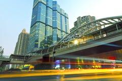 De ljusa slingorna av bilarna i den moderna staden Arkivfoto