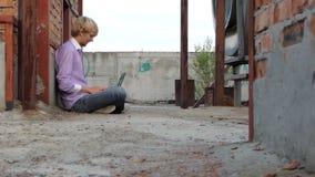 De Loafingsmens zit op een bouwwerf en werkt bij zijn laptop stock videobeelden