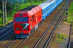 De locomotief die de auto's van een passagierstrein trekken Stock Afbeelding