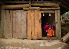 De lokale Hmong-vrouw van de heuvelstam gebruikt naaimachine terwijl haar dochter voor foto stelt Stock Afbeelding