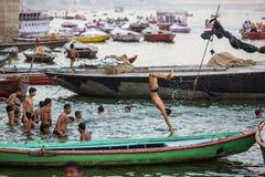 De lokale jeugd duikt in de rivier van water heilige Ganges bij avond Royalty-vrije Stock Afbeeldingen