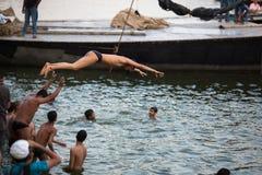 De lokale jeugd duikt in de rivier van water heilige Ganges bij avond Stock Fotografie