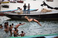 De lokale jeugd duikt in de rivier van water heilige Ganges bij avond Royalty-vrije Stock Foto