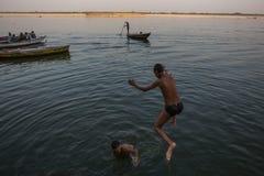 De lokale jeugd duikt in de rivier van water heilige Ganges bij avond Stock Afbeeldingen