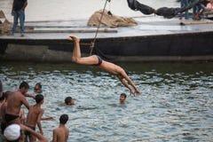 De lokale jeugd duikt in de rivier van water heilige Ganges bij avond Royalty-vrije Stock Foto's