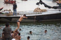 De lokale jeugd duikt in de rivier van water heilige Ganges bij avond Stock Foto's