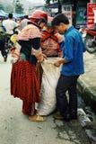 de lokale leden die van de bloem hmong stam wat korrels en opbrengst inpakken aan een grote plastic zak bij de lokale landbouwers stock fotografie