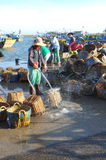 De lokale vrouwen maken hun manden schoon die voor het vervoeren van vissen van de boot aan de vrachtwagen werden gebruikt Royalty-vrije Stock Fotografie
