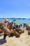 De lokale vrouwen maken hun manden schoon die voor het vervoeren van vissen van de boot aan de vrachtwagen werden gebruikt Royalty-vrije Stock Foto's