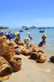 De lokale vrouwen maken hun manden schoon die voor het vervoeren van vissen van de boot aan de vrachtwagen werden gebruikt Stock Foto