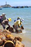 De lokale vrouwen maken hun manden schoon die voor het vervoeren van vissen van de boot aan de vrachtwagen werden gebruikt Stock Fotografie