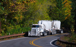 De long-courrier remorques en vrac de camion semi sur la route d'enroulement d'automne Photos stock
