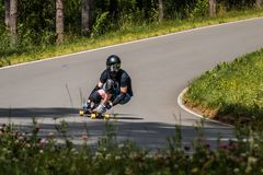 De Longboard bergaf ruiter maakt snel in een draai royalty-vrije stock fotografie