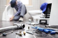 De loodgieter aan het werk in een badkamers, de dienst van de loodgieterswerkreparatie, assembleert