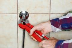 De loodgieter bevestigt een pijp stock fotografie
