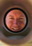 De loodgieter die van Smling onderaan rioolbuis kijkt Stock Afbeelding