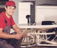De loodgieter herstelt de pijpen De mannelijke reparaties van de specialistenloodgieter royalty-vrije stock afbeelding