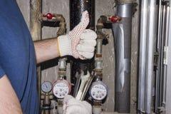 De loodgieter met de moersleutels in handen houdt duim tegen Tegen achtergrond van pijpen en van drukmaten loodgieterswerkarbeide Stock Afbeeldingen
