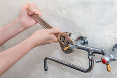 De loodgieter overhandigt het bevestigen waterkraan met moersleutel, omhoog sluit royalty-vrije stock foto