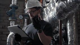 De loodgieter in technische ruimte spreekt in het audiobericht van de sprekerstelefoon stock video