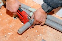 De loodgieterarbeider met schaar snijdt de buis scherpe metaal-plastic pijp door speciale rode schaar Loodgieterhanden het werken Royalty-vrije Stock Fotografie
