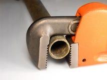 De loodgieters leiden Moersleutel door buizen stock afbeelding