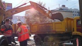 De loodgietersarbeiders graven een geulgraafwerktuig, noodsituatiereparatie stock video