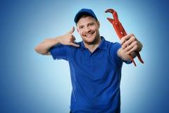 De loodgieterswerkdiensten - loodgieter met moersleutel die telefoongesprekgebaar tonen stock foto
