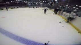 De loodpuck van de hockeyspeler met stok aan tegenovergestelde teampoort stock footage