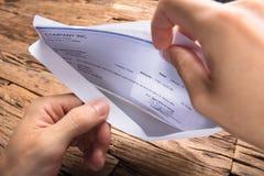 De Looncheque van zakenmanopening envelope with stock foto's
