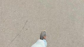 In de loop van de dag het lopen op het asfalt in grijze tennisschoenen stock footage