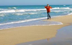 De looppas van de mens in rode t-shirt op zand op kust royalty-vrije stock afbeeldingen