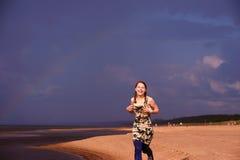 De looppas van het tienermeisje langs het strand Stock Foto